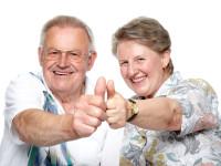 Closeup portrait of a smiling elderly couple showing thumps