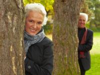 Lachendes Paar hinter Bäumen