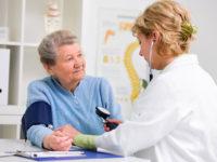 rztin misst den Blutdruck und Puls bei Patientin