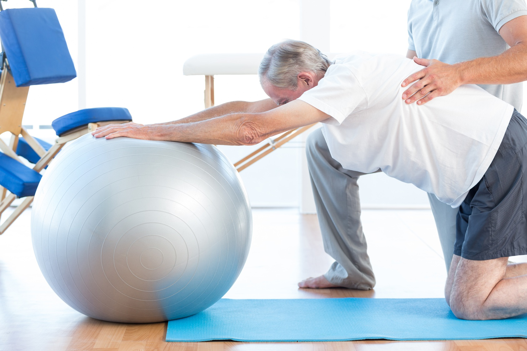 Physiotherapist helping man with exercise ball