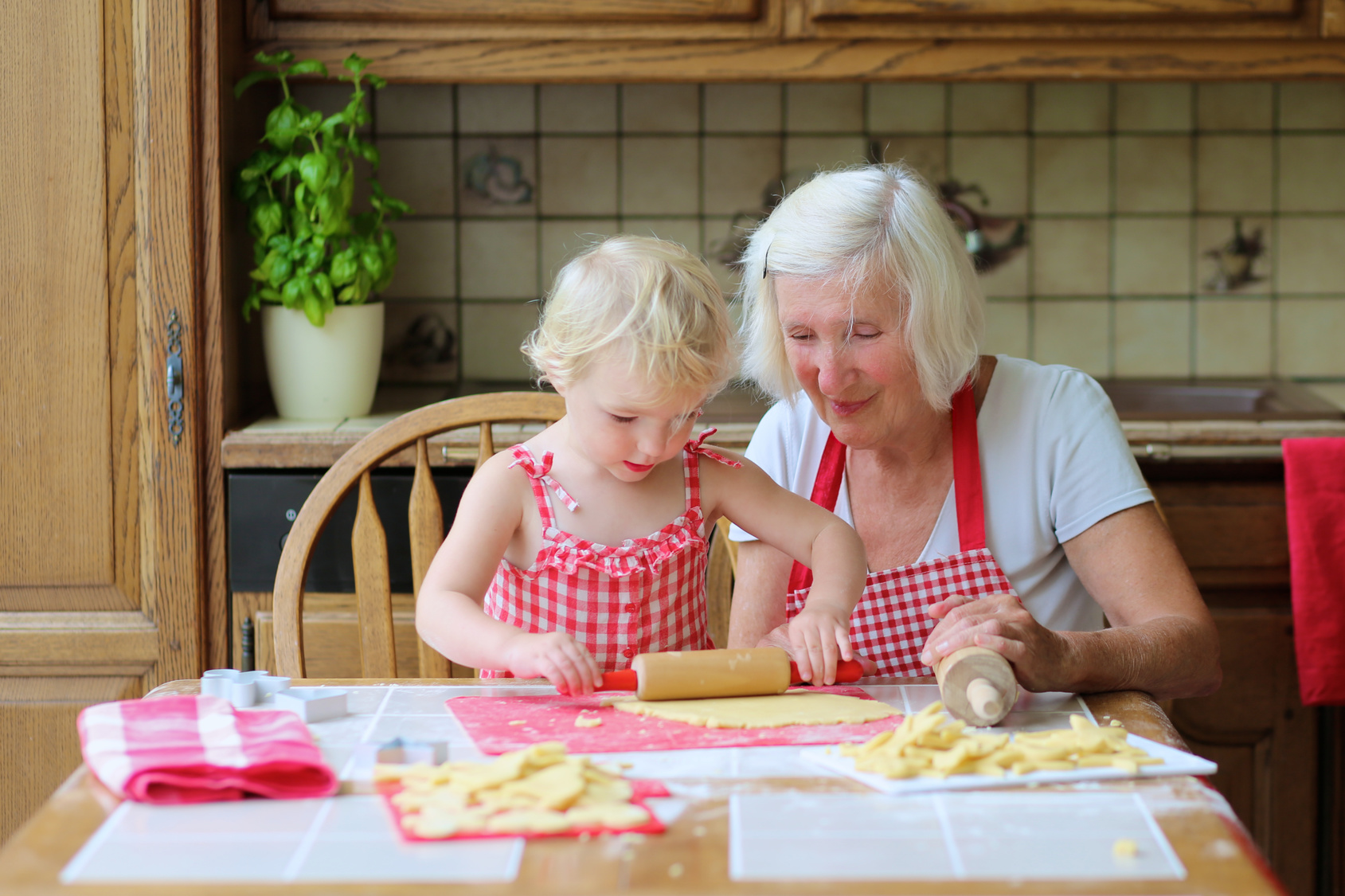 Grandmother and granddaughter preparing cookies in the kitchen