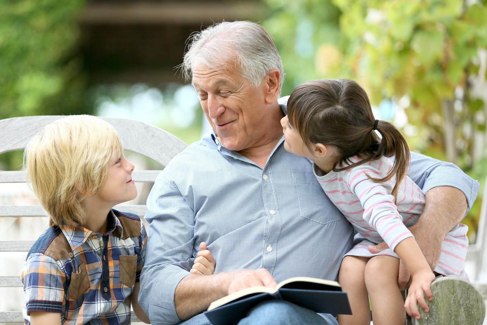 Senior man reading book with grandkids