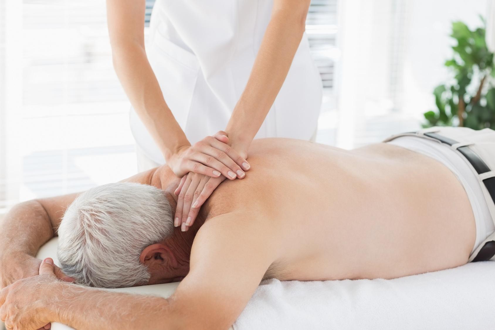 Therapist massaging back of senior patient