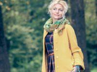 trendy Beautiful senior woman in a yellow coat walks in the park