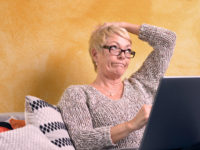 Aktive Rentnerin schaut besorgt auf Ihr Laptop