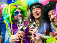 Happy girls and boys at Carnival Party clinking glasses with champagne