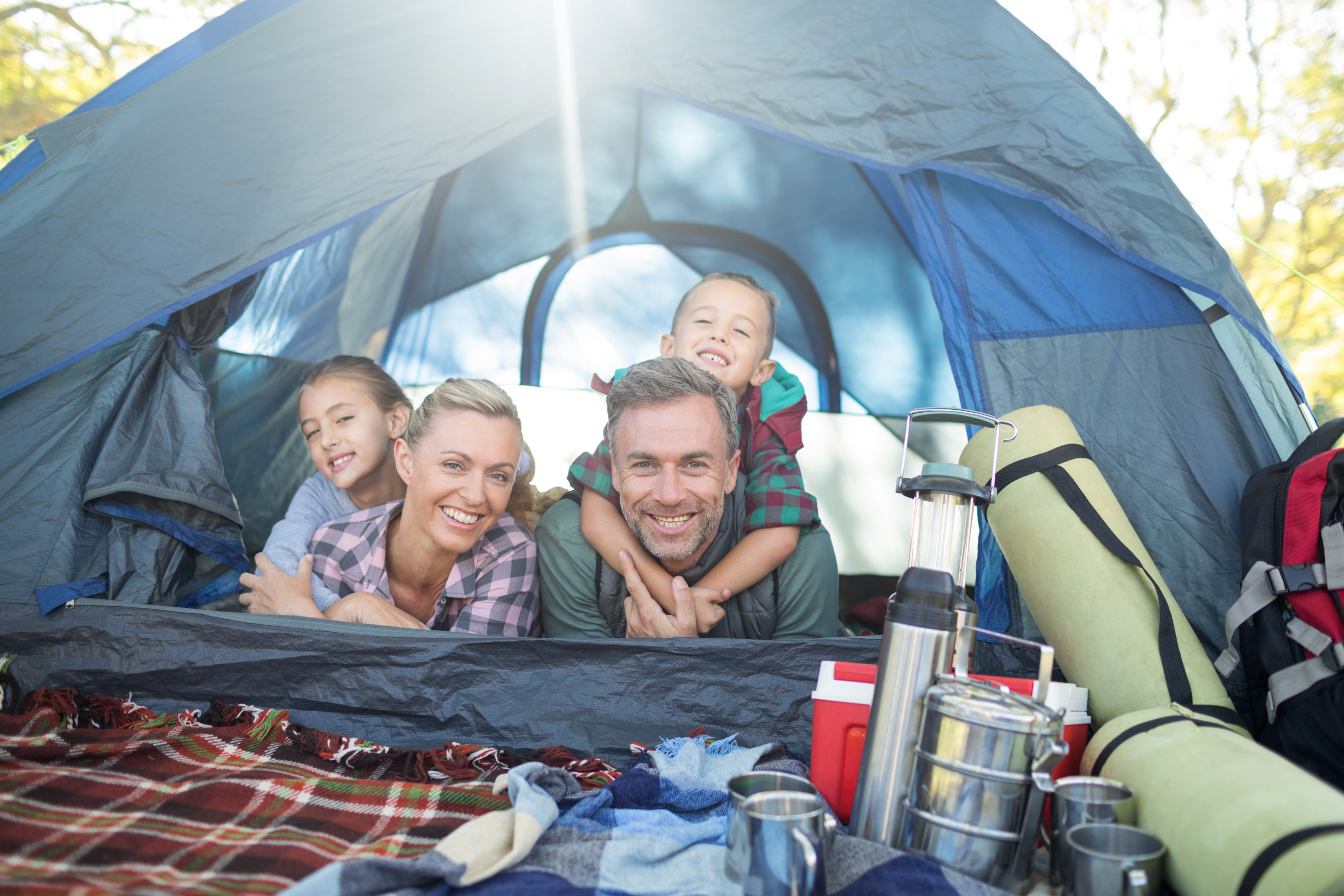 Smiling family lying in the tent